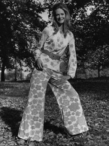 Schöne Frau in den 70er Jahren Mode in einem 70er jahre Raum